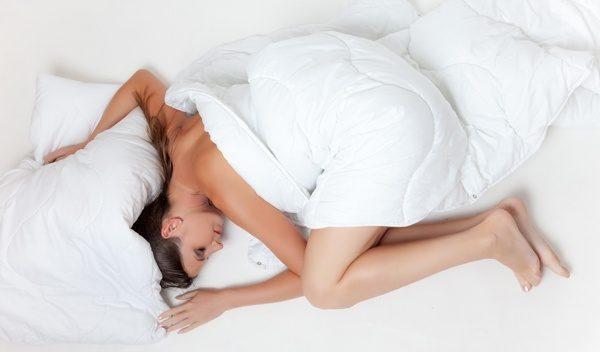 femeie ce se relaxează pe o saltea de pat